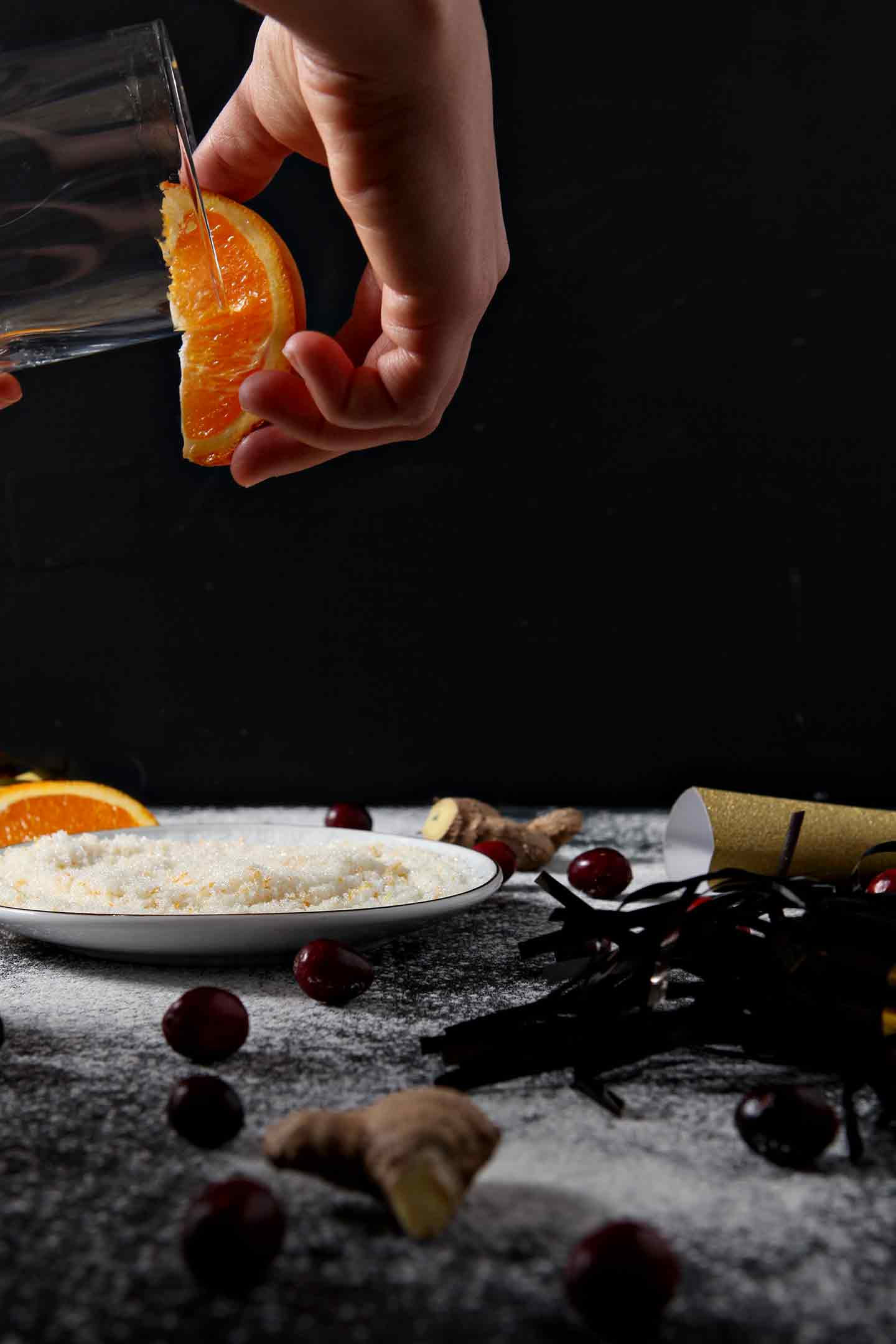 An orange is rubbed along the rim of a glass before it is dipped in orange sugar