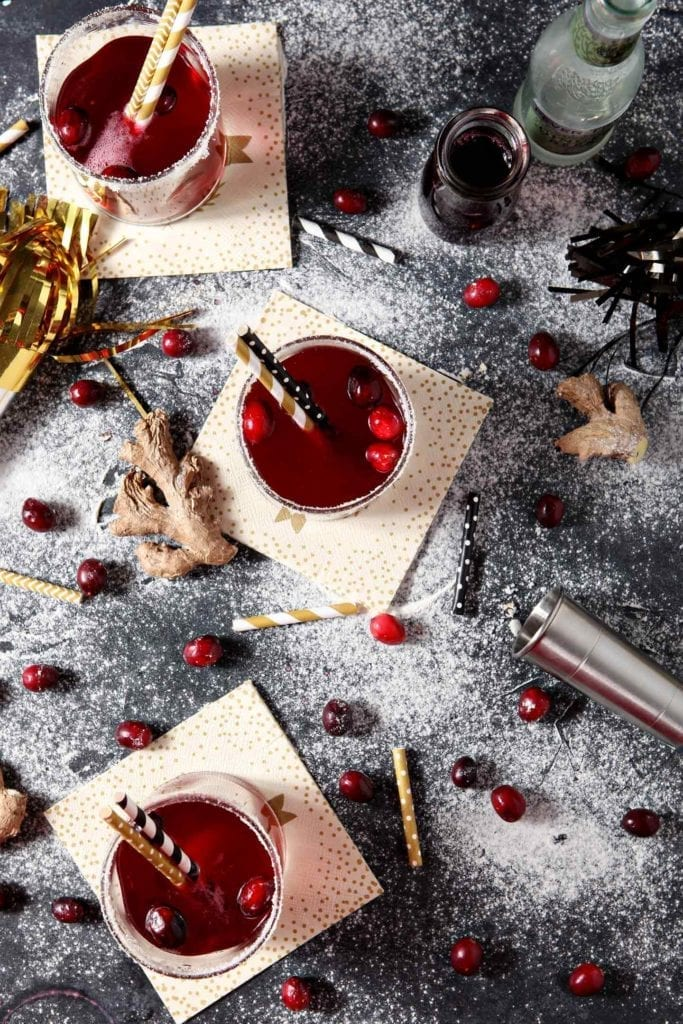 "Three glasses ofSparkling Ginger Cranberry Mocktails are shown from above on a black board, surrounded by cranberries, ginger and ""snow"""