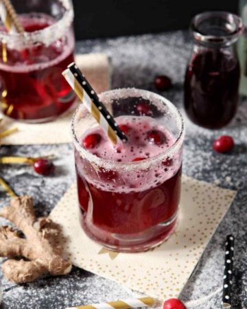 Two Sparkling Ginger Cranberry Mocktails are shown on a dark background, surrounded by fresh cranberries and ginger
