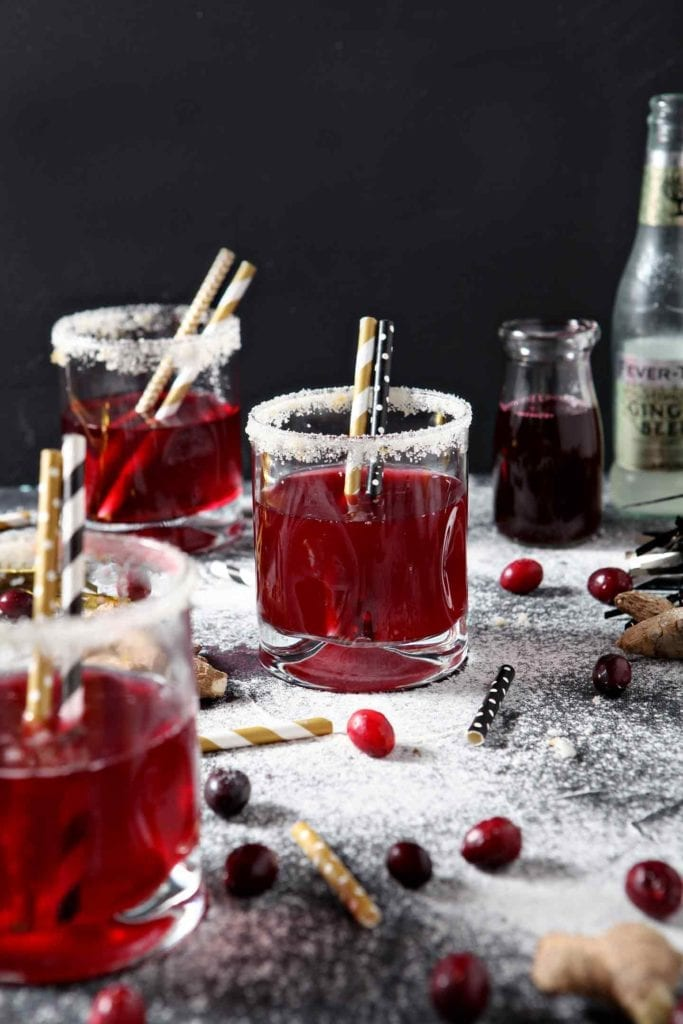 Three Sparkling Ginger Cranberry Mocktails are served on napkins with golden straws