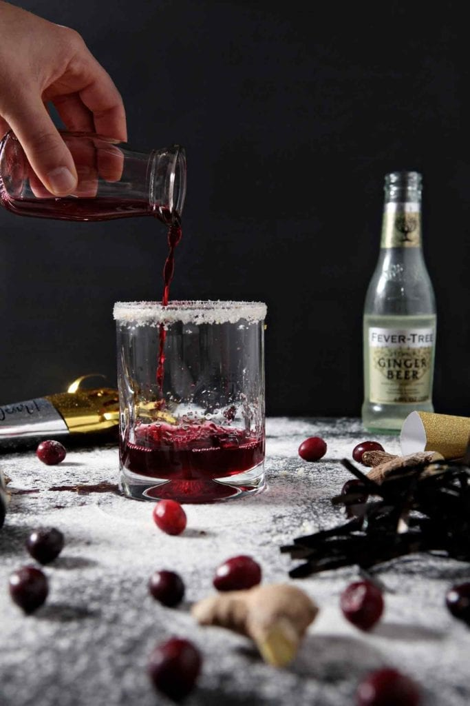 Cranberry juice is poured into a glass to make a Sparkling Ginger Cranberry Mocktail