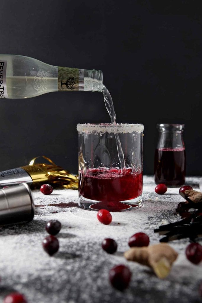 Ginger beer is poured into a glass to make a Sparkling Ginger Cranberry Mocktail