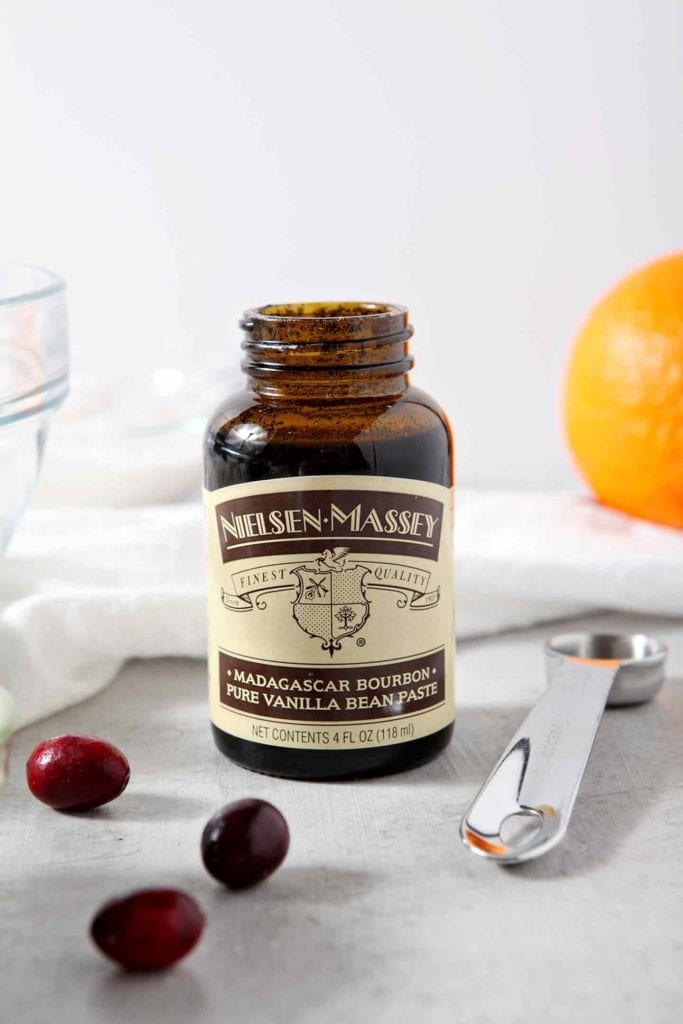 A bottle of Vanilla Bean Paste sits on a grey tabletop with a measuring spoon