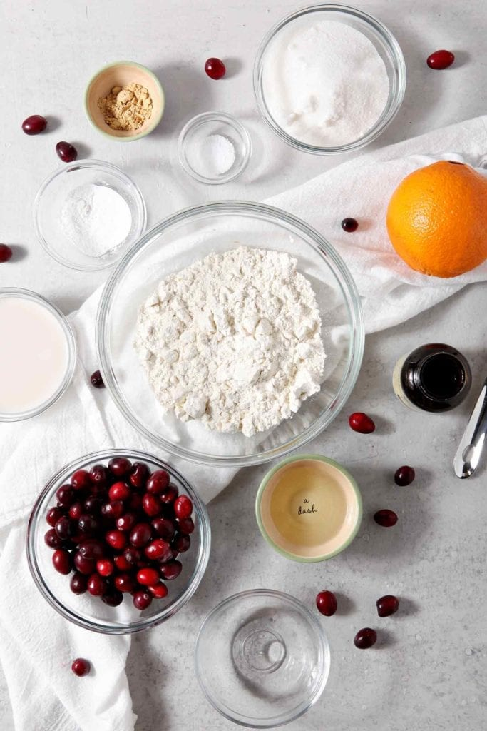 Ingredients for Vegan Orange Cranberry Muffins are shown on a grey tabletop, surrounded by fresh cranberries