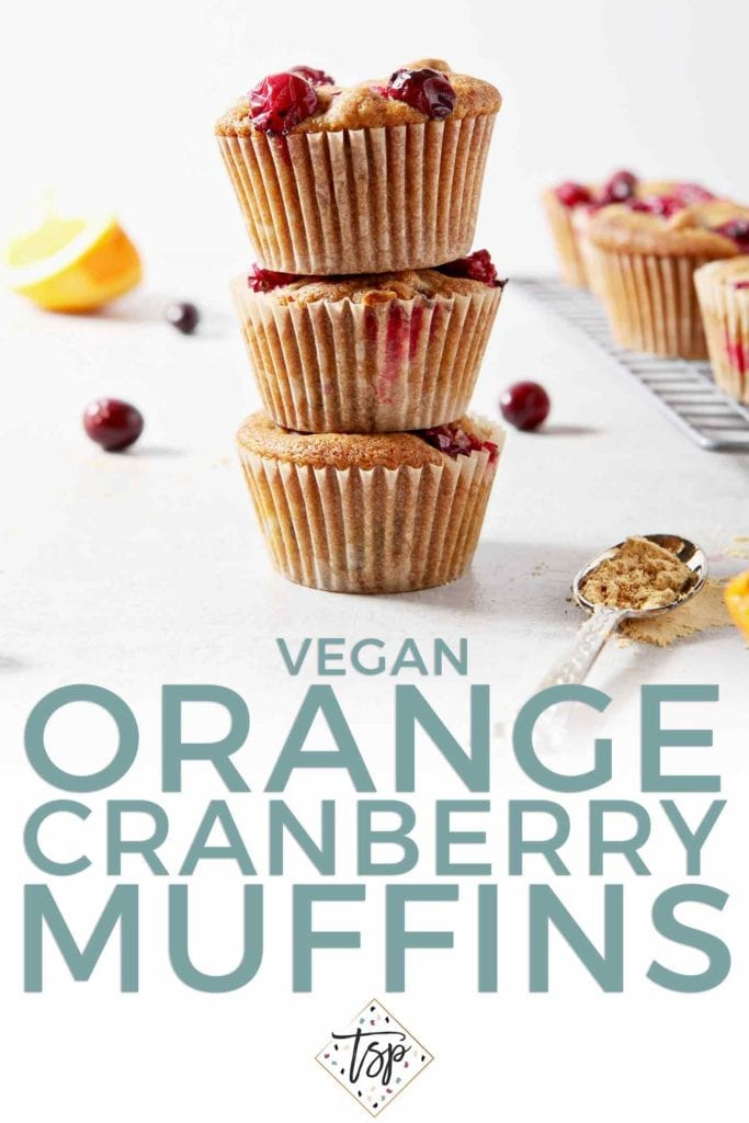 A stack of three Vegan Orange Cranberry Muffins stand beside a wire cooling rack with more muffins, shown with text