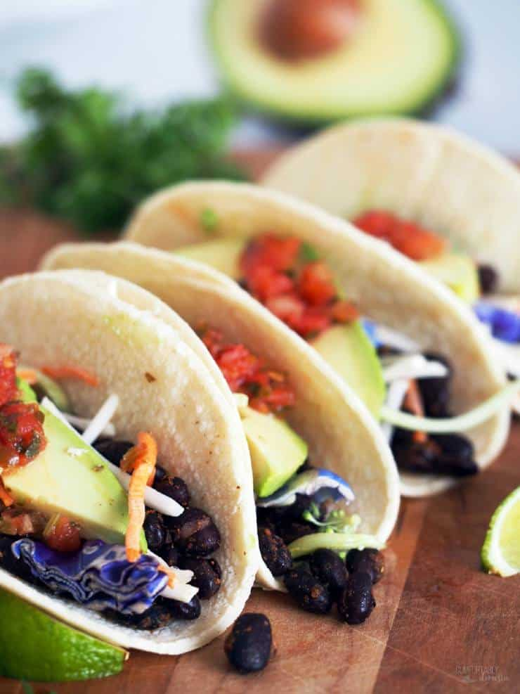 Four Roasted Black Bean Tacos are served on a wooden plate with all the fixings