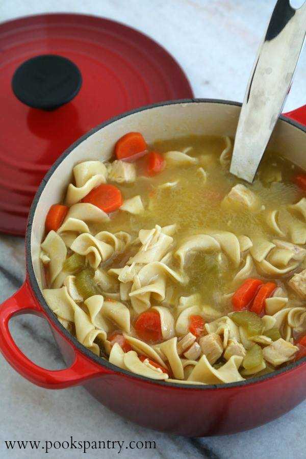 A red Dutch oven holds a batch of Classic Chicken Noodle Soup