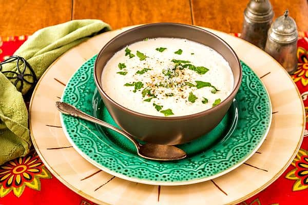 A bowl of Cream of Cauliflower Soup (Keto) sits on top of a green plate with a spoon