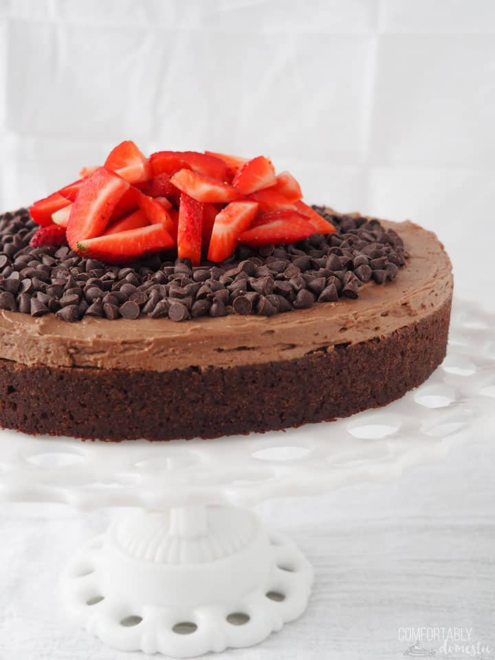 A Gluten Free Chocolate Fudge Cake sits on a white cake stand, garnished with chocolate chips and strawberries