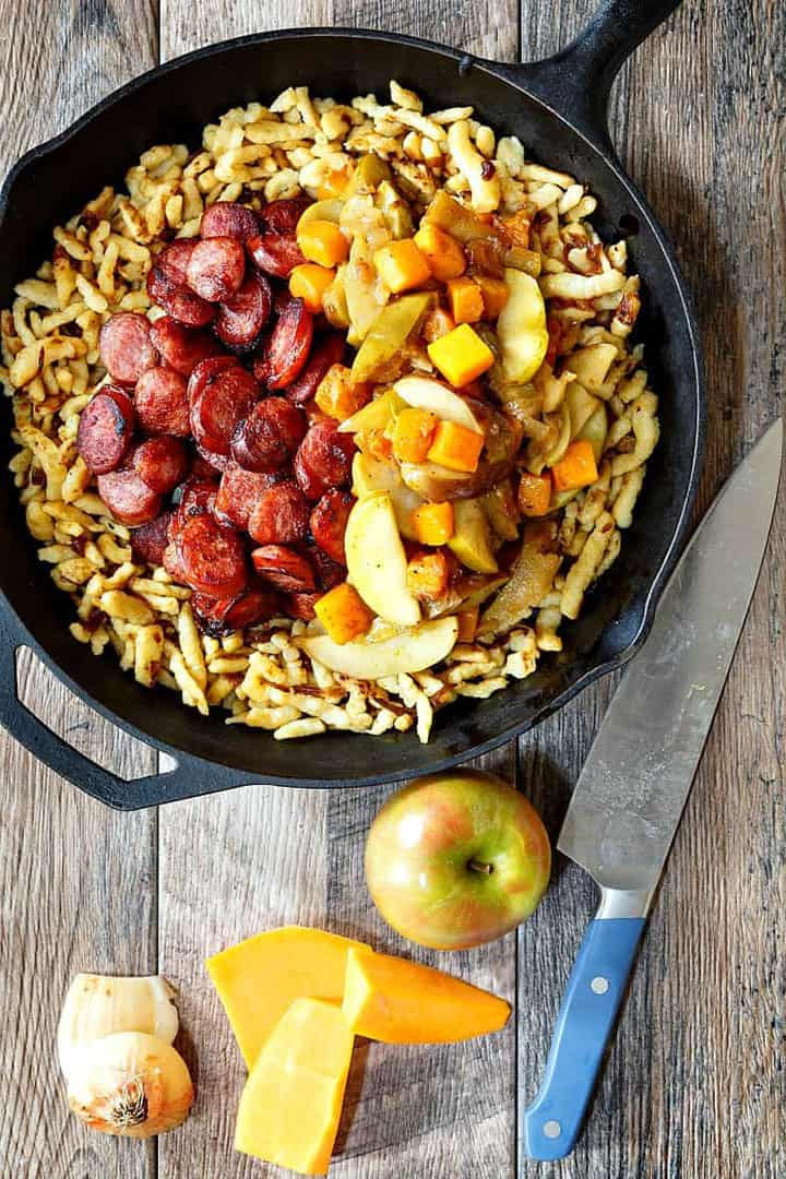 Overhead image of Polish Sausage with Apples, Onions, and Butternut Squash, shown in a skillet, with the ingredients and a knife beside it on a wooden board
