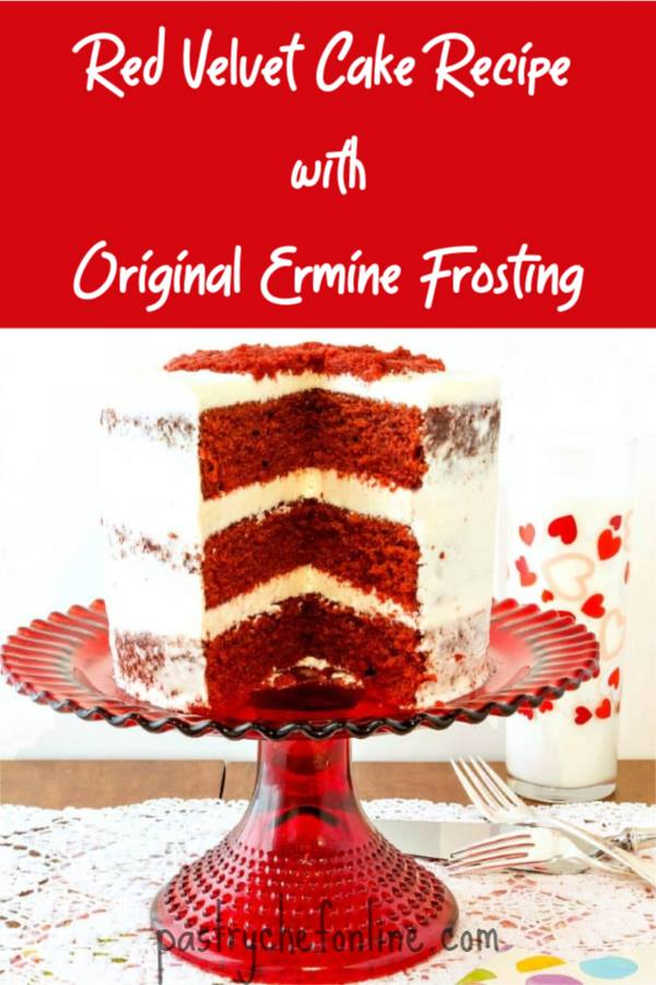 A Red Velvet Cake with Ermine Frosting sits on a red cake stand with one slice taken out