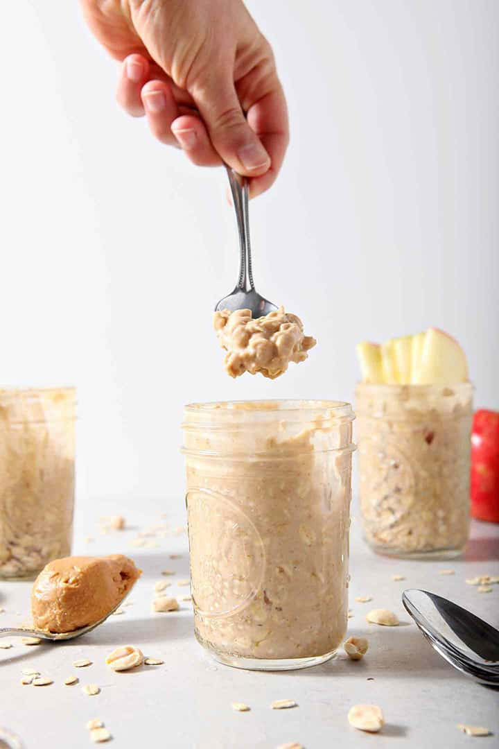 A woman lifts a spoonful of Peanut Butter Overnight Oats out of a mason jar
