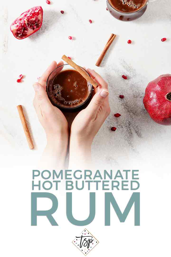 A woman holds a mug of Pomegranate Hot Buttered Rum in this Pinterest graphic