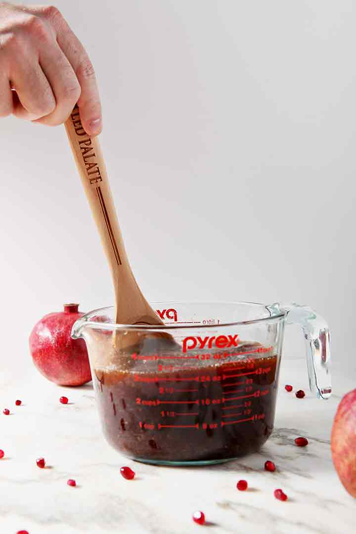 A man stirs Pomegranate Hot Buttered Rum in a glass measuring cup with a wooden spoon