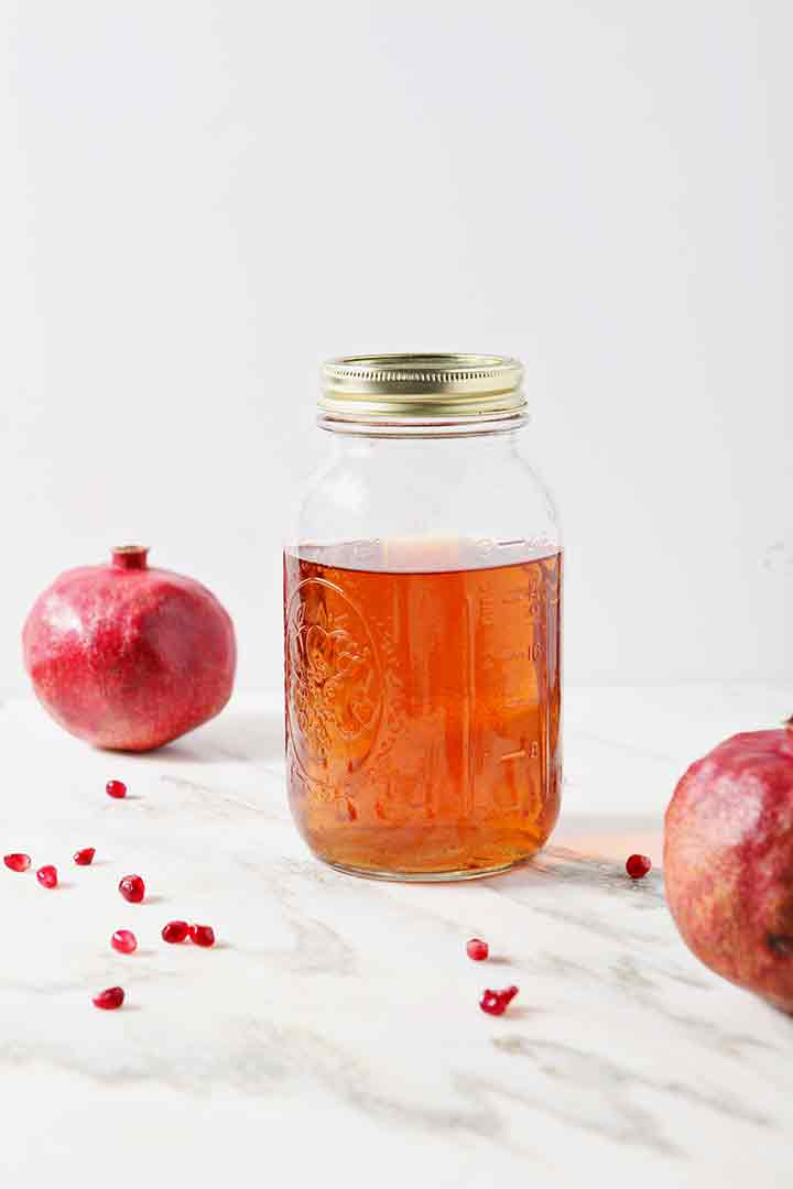 A jar holds Pomegranate-Infused Rum to make a Pomegranate Hot Buttered Rum