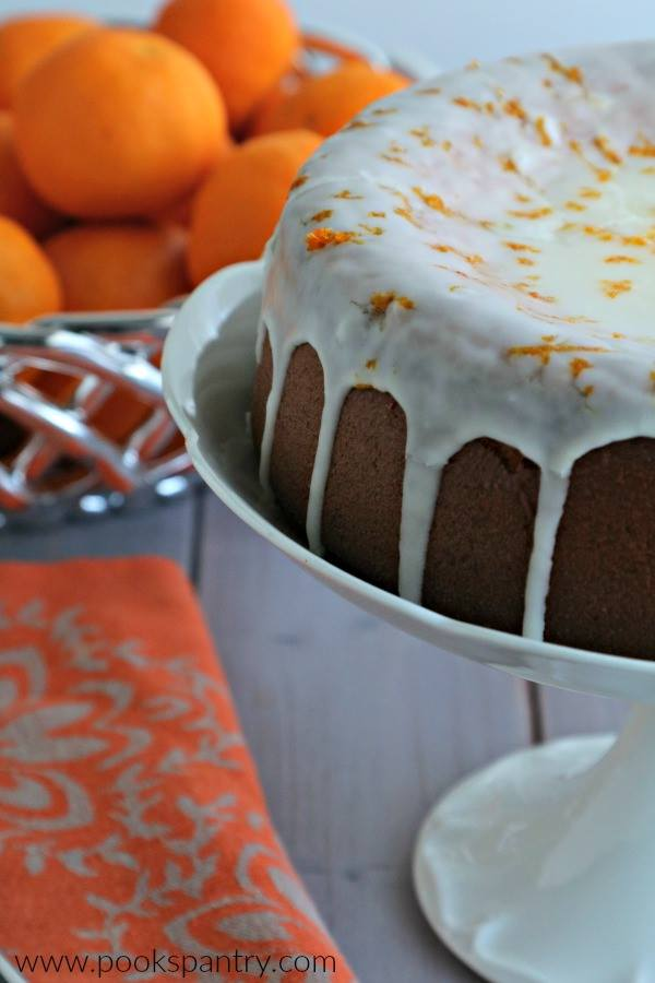 A Gluten Free Clementine Cake sits on a white cake stand, drizzled with glaze