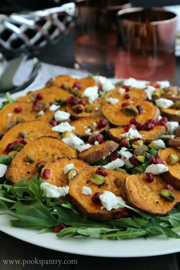 A white platter holds a beautifully laid out Superfood Salad with Pomegranate and Sweet Potatoes