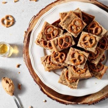 Boozy Bacon Pretzel Peanut Butter Bars are served on a round white plate