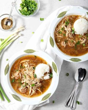Two bowls of Chicken and Sausage Gumbo are served with rice and green onions
