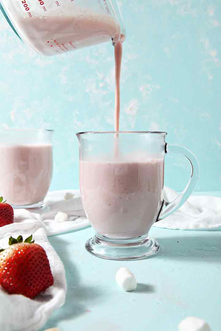 Strawberry White Hot Chocolate is poured into a mug