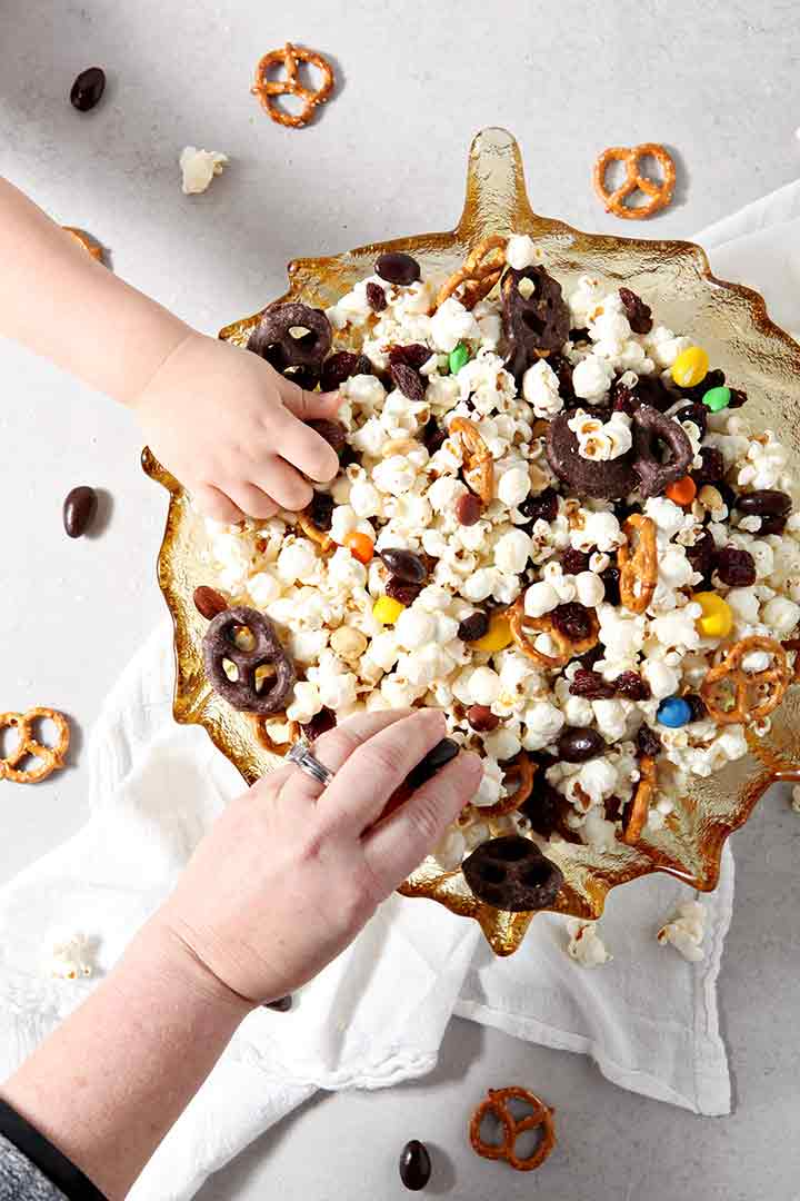 Two people reach into a bowl of Sweet-and-Salty Popcorn Mix