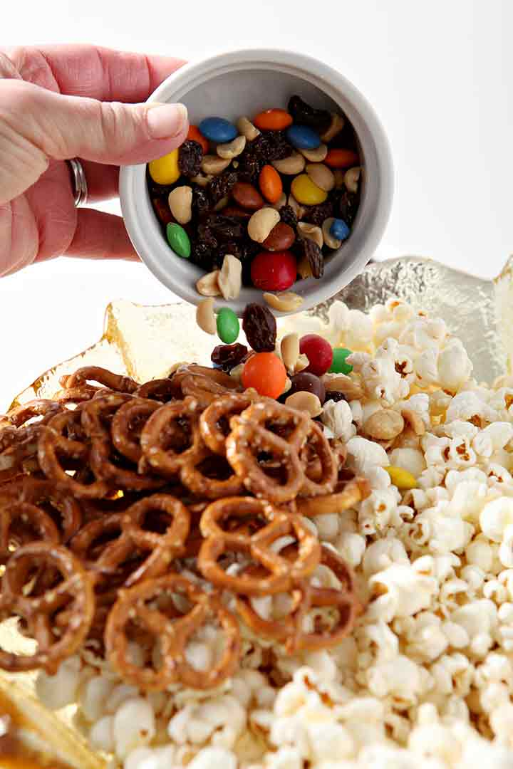 Trail mix is added to the bowl