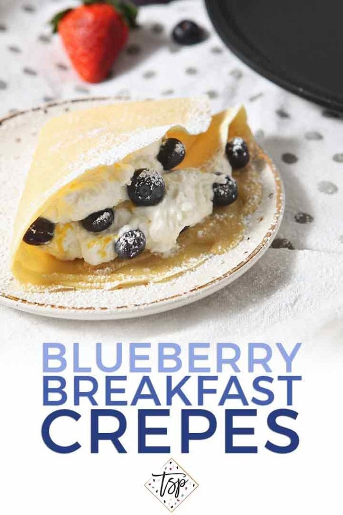 Close up of a Blueberry Crepe on a plate, sprinkled with powdered sugar