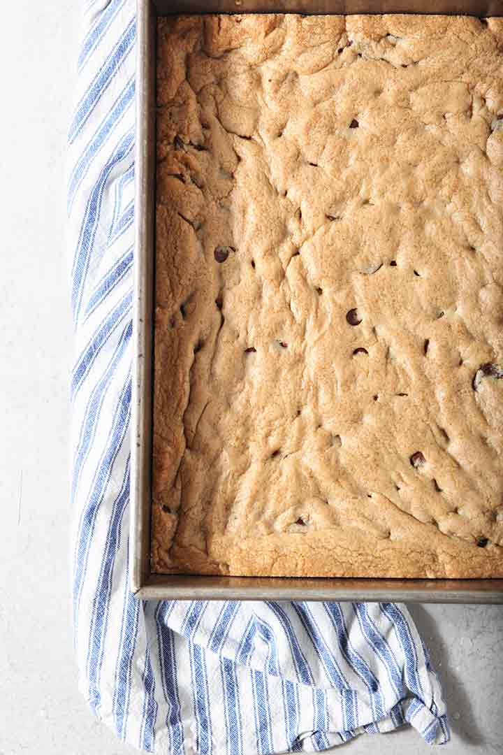 A pan of Chocolate Chip Cookie Bars cools on a countertop
