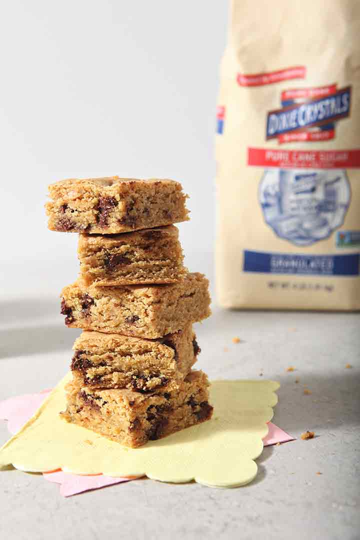 Cookie bars are stacked in front of a bag of Dixie Crystals sugar