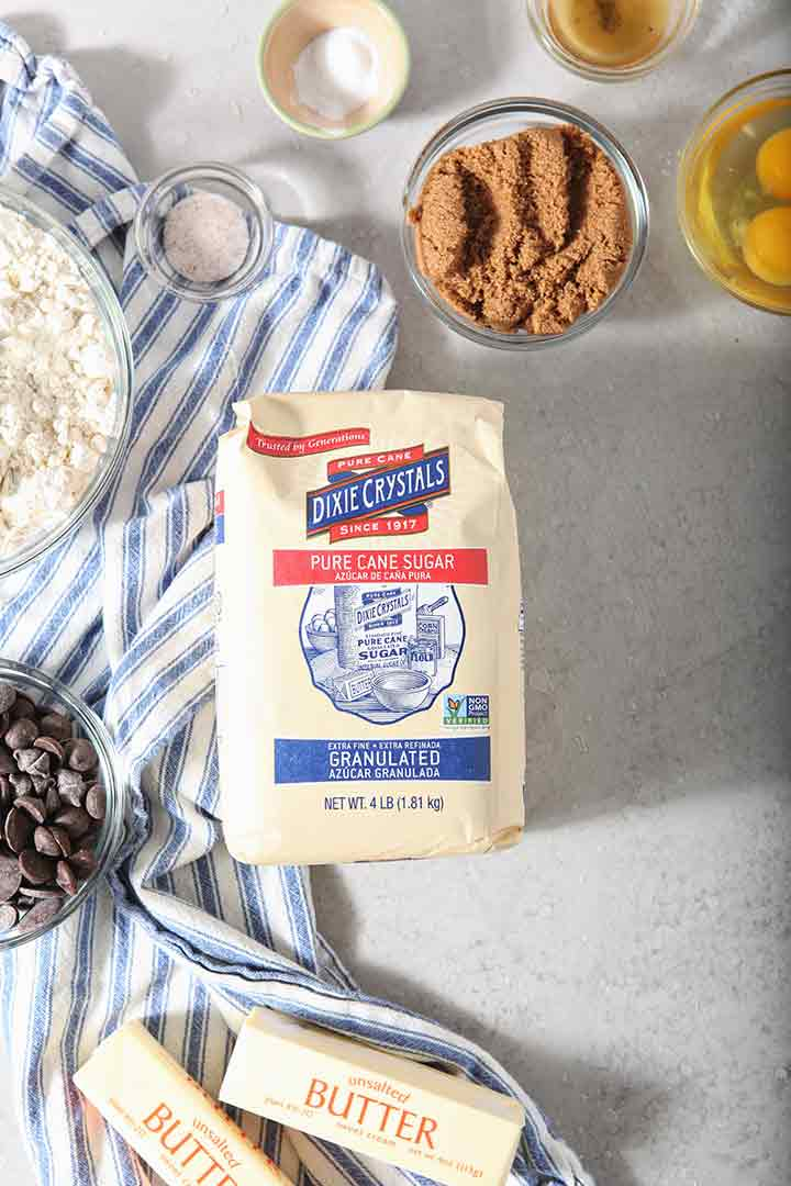 Ingredients to make Chocolate Chip Cookie Bars are laid out on a grey backdrop