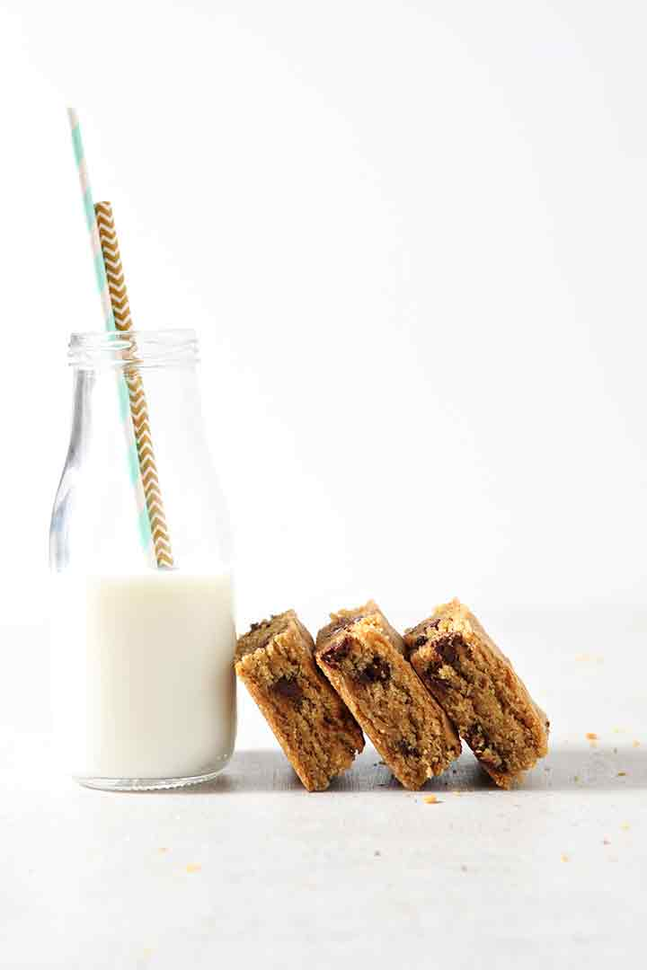 Cookie bars lean up against the side of a milk glass