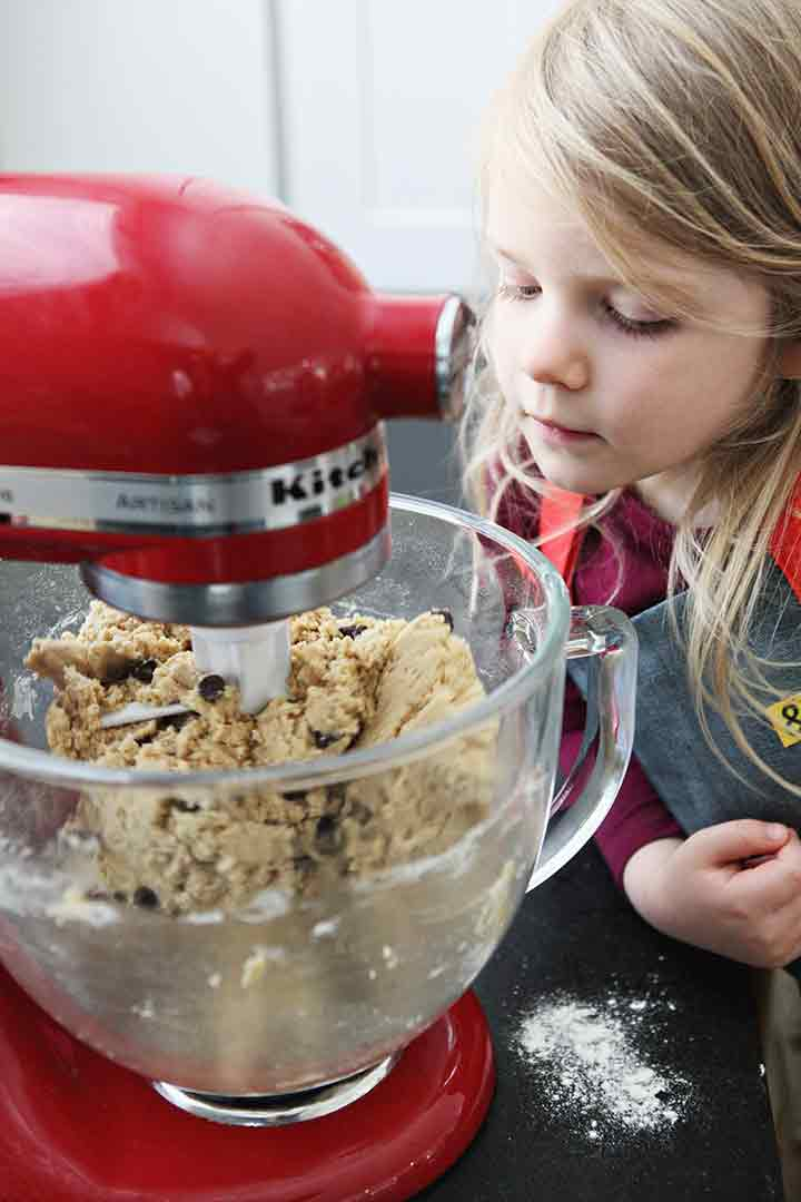 A girl watches Chocolate Chip Cookie Bar batter mix in a stand mixer