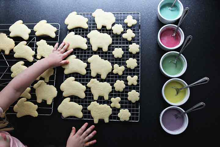 A girl touches lemon sugar cookies as they cool on wire racks