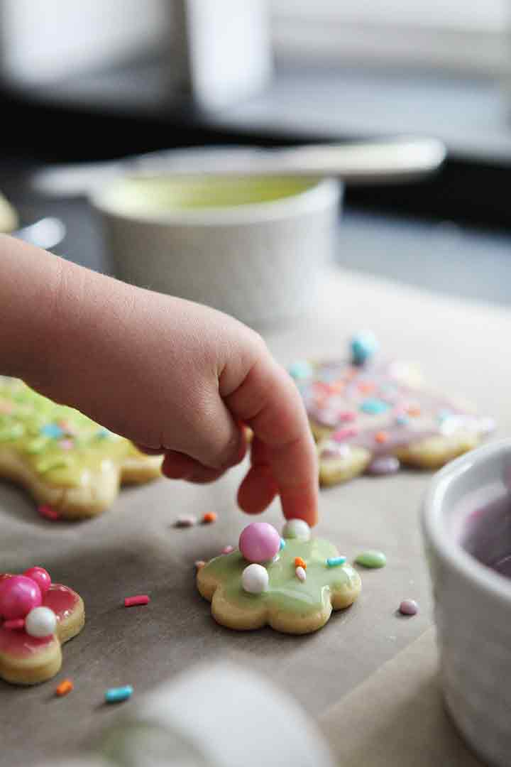 A girl places decorative sprinkles onto lemon sugar cookies