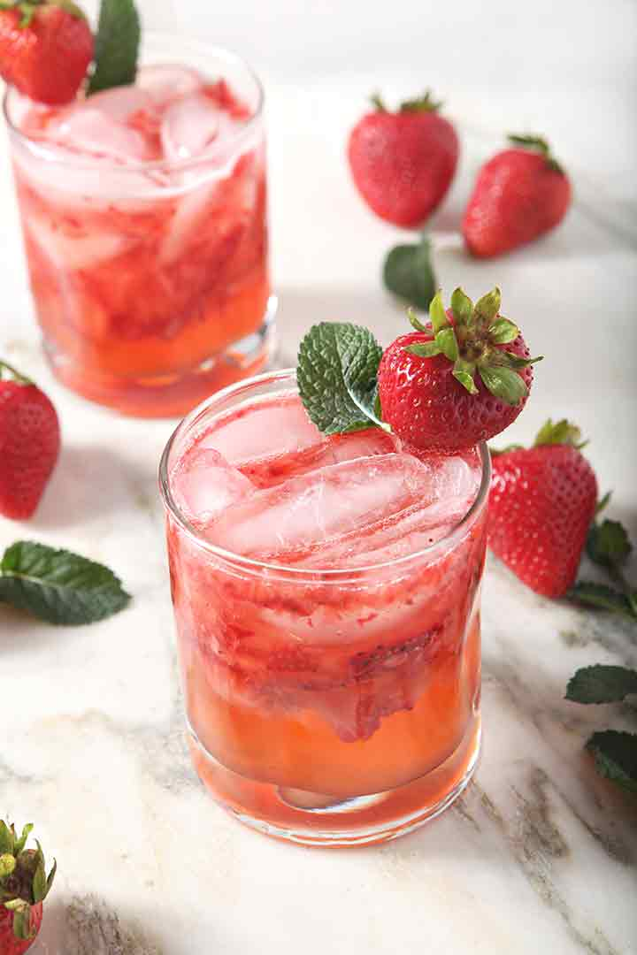 Two Strawberry Moscow Mules are served on a marble background