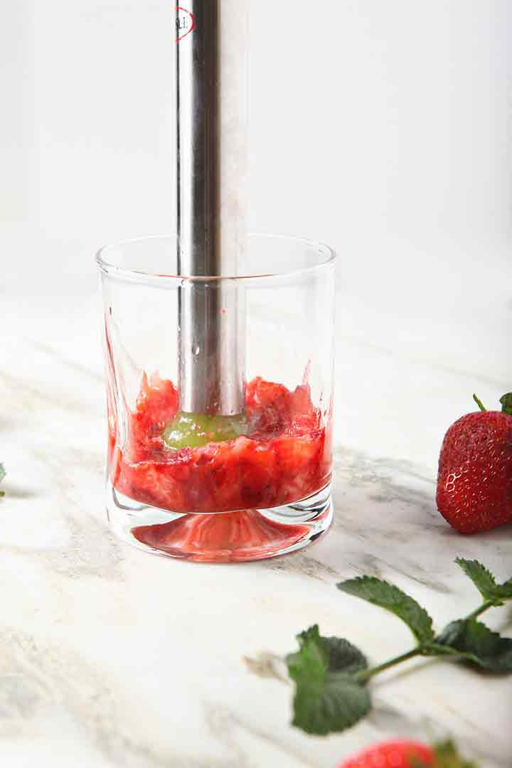 Strawberries are muddled in a glass