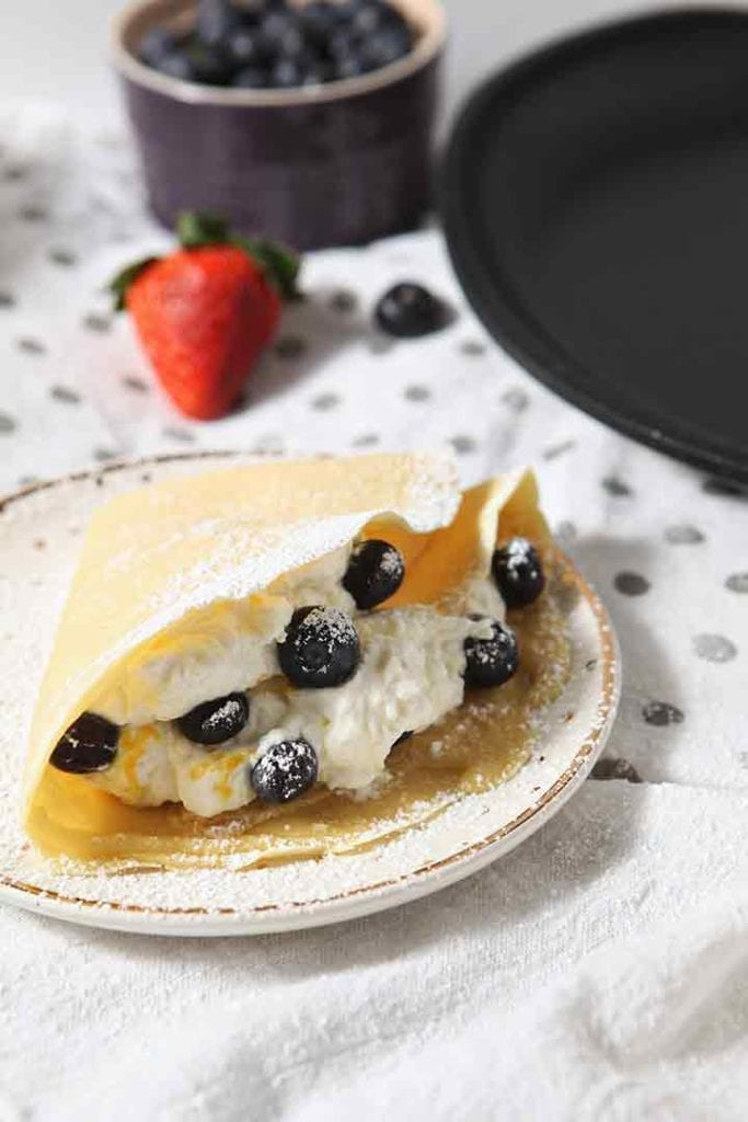 A blueberry crepe is served on a plate, sprinkled with powdered sugar and fresh whipped cream