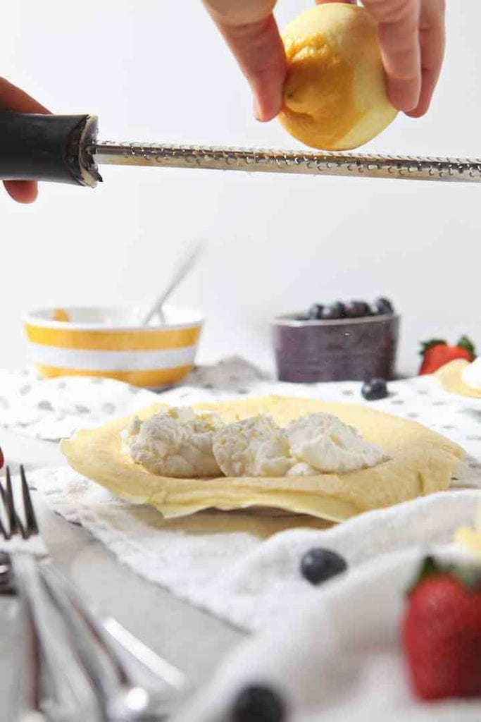 A lemon is zested on top of a sweet crepe and its whipped cream filling before fruit is added