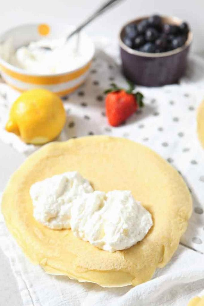 Lemon Whipped Cream is shown in a homemade crepe before fruit is added
