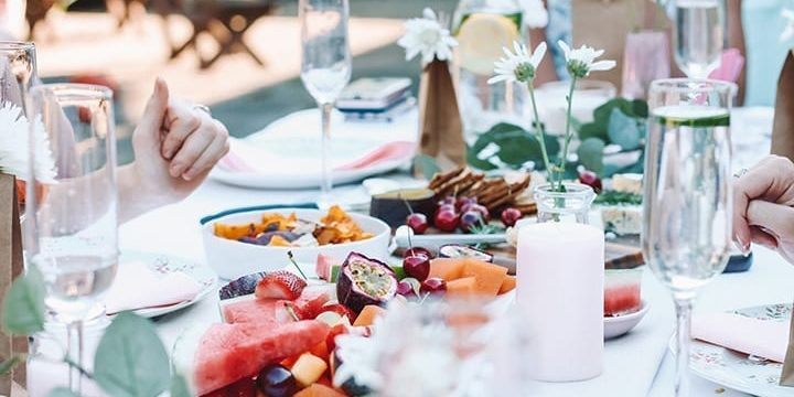 Women gather around a pink decorated table for homemade food and rose