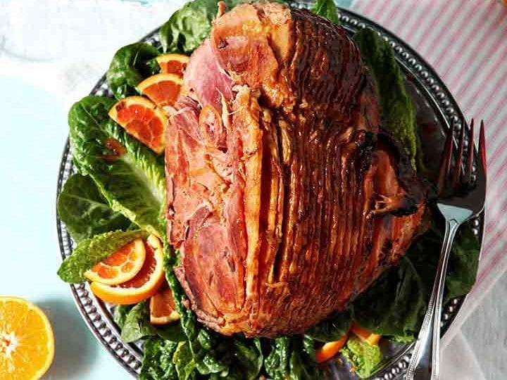 A Baked Ham with Bourbon Orange Glaze sits on a platter, ready for serving