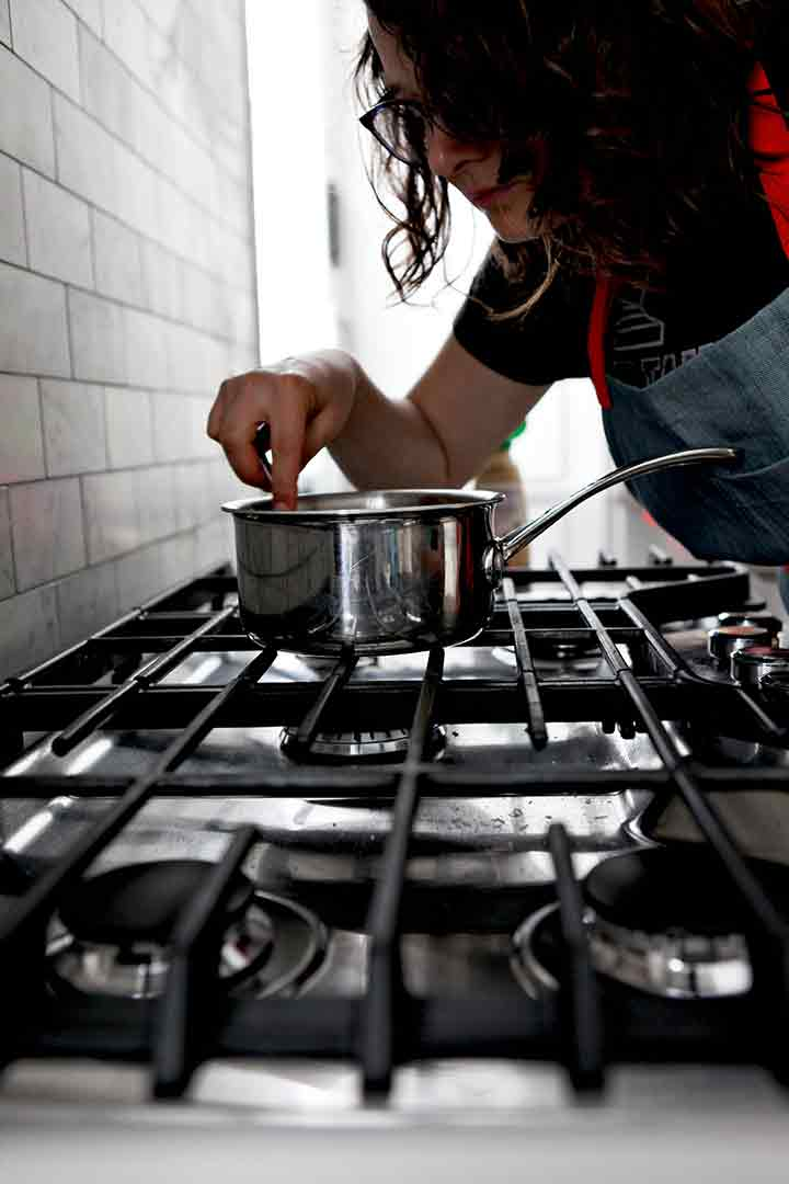 A woman stirs the bourbon orange glaze on the stovetop as it cooks down