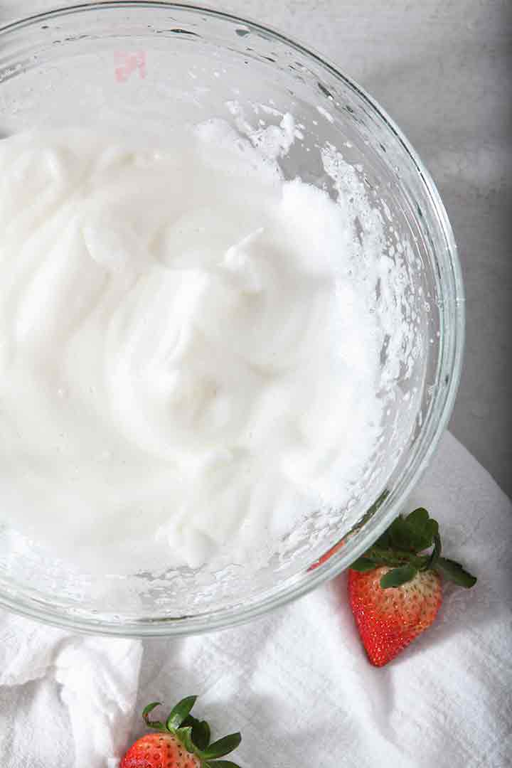 A bowl of whipped egg whites, made into soft peaks, are shown