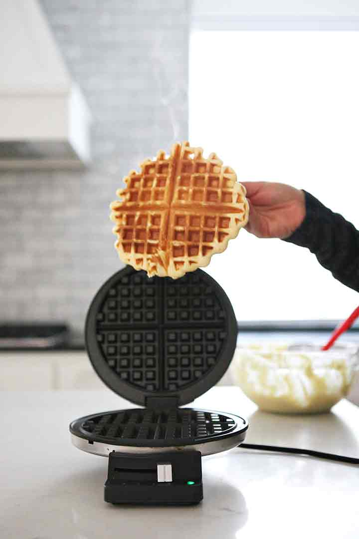 A woman pulls a hot waffle off the waffle iron