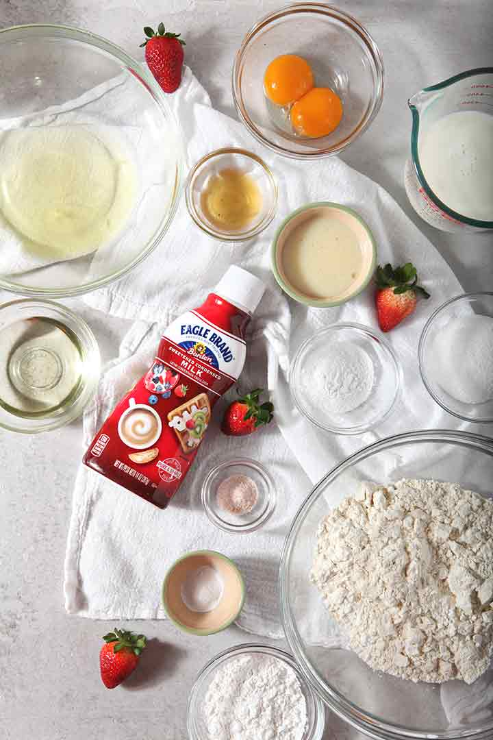Strawberries and cream waffle ingredients are laid out on a flat surface