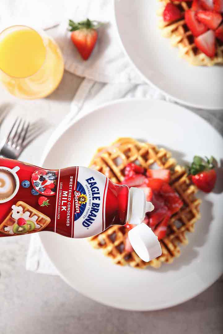 Eagle Brand sweetened condensed milk is drizzled onto waffles, from above