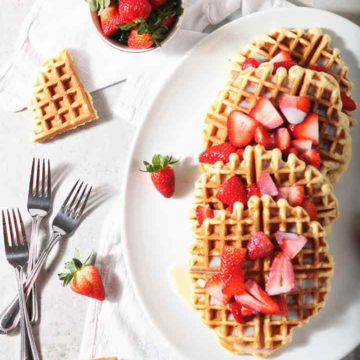 Homemade Waffles with Strawberries and Cream are served on a platter