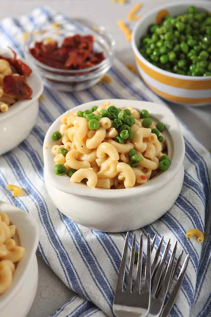 Close up of Instant Pot Macaroni and Cheese, served with steamed peas