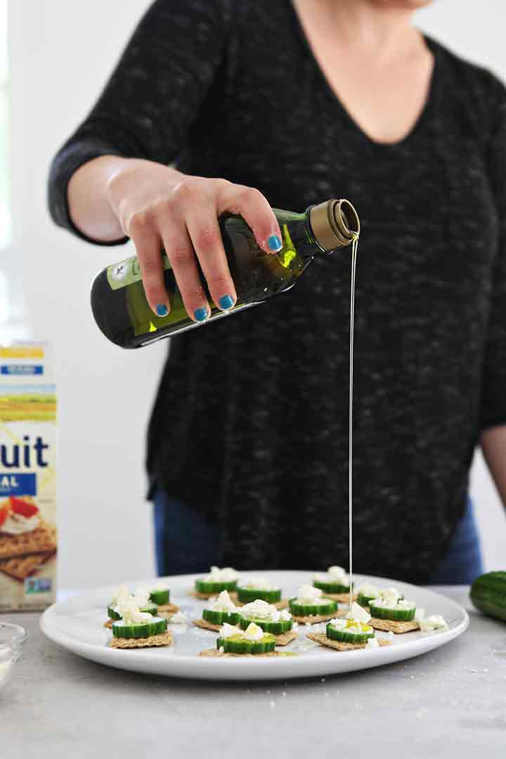 A woman drizzles olive oil on top of the cucumber appetizer