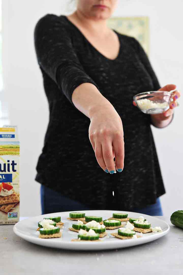 A woman sprinkles feta cheese over a cucumber appetizer